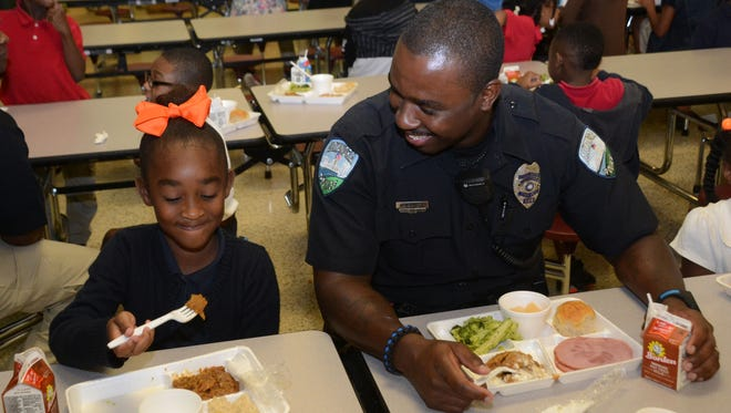 Alexandria Police Officer Kendric Baker (left) sits next to his daughter, first-grader Karissa Baker, as he has lunch with her and Acadian Elementary School students Tuesday. His visit is part of a voluntary program APD began to build positive relationships with kids by having lunch with students at different schools every day.