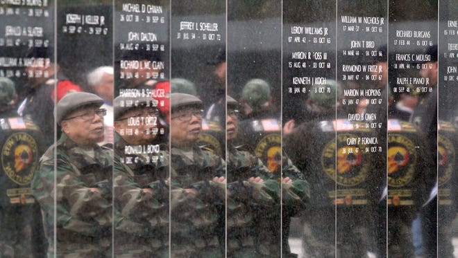 Vietnam veteran Pran Chinh, Cherry Hill, is reflected in the walls of the New Jersey Vietnam Veterans' Memorial in Holmdel during the 2015 Veterans Day Ceremony there.