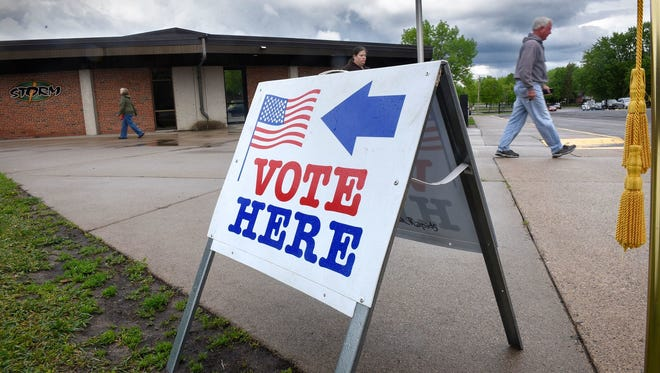 Voters walk past a sign pointing to the polls at Pleasantview Elementary School Tuesday, May 23, 2017, in Sauk Rapids.