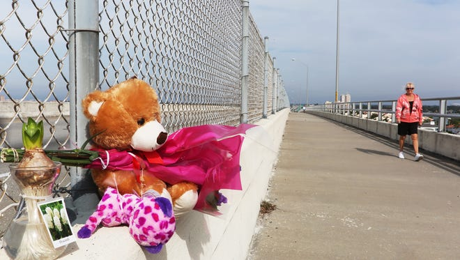 A pedestrian walks near a memorial for  5-year-old Phoebe Jonchuck on Friday, Jan. 9, 2015, that has been set up atop of the Dick Misener Bridge, St. Petersburg, Fla.,  Jonchuck was thrown from the bridge by her father, John Jonchuck Jr., according to police.