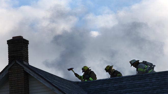 Members of the Hilton Fire Department vent a roof at a house fire on Railroad Avenue in Hilton Tuesday.The fire started between the first and second floors of the duplex home, said Hilton Fire Chief Joe Lissow. One resident home during the fire was uninjured, Lissow said. Firefighters responded to the fire about 9 a.m.