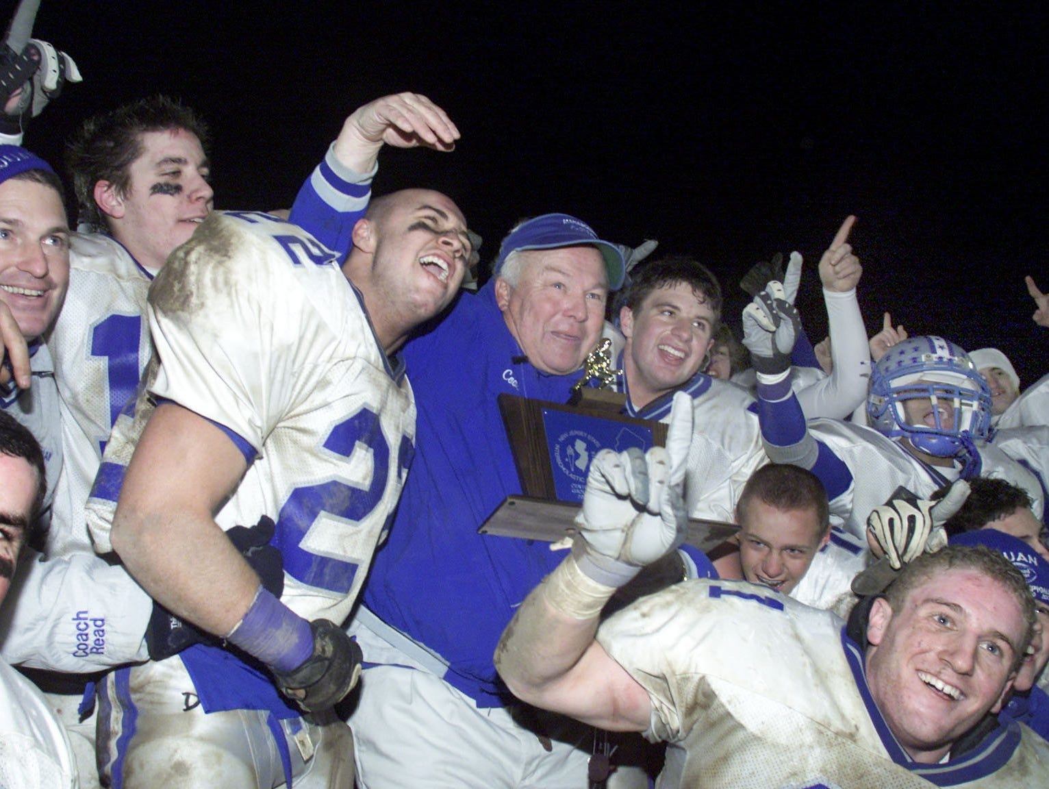 Manasquan coach Vic Kubu is surrounded by his players after their 2002 win at New Brunswick gave them their fifth straight state sectional title.