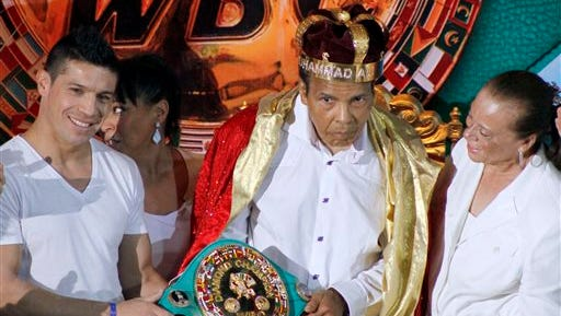 """In this file photo, the former heavyweight boxing champion Muhammad Ali, center, is crowned """"King of Boxing"""" while accompanied by his wife, Lonnie, right, and Argentine boxer Sergio Martinez during the 50th convention of the World Boxing Council in Cancun, Mexico. Spokesman Bob Gunnell said Saturday that the 72-year-old boxing great has been hospitalized with a mild case of pneumonia and is in stable condition."""