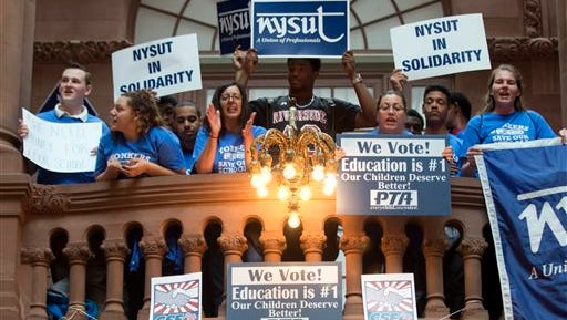 Supporters of the Yonkers school district hold signs during a rally on the Great Western Staircase at the Capitol on Tuesday, May 19, 2015, in Albany, N.Y. (AP Photo/Mike Groll)