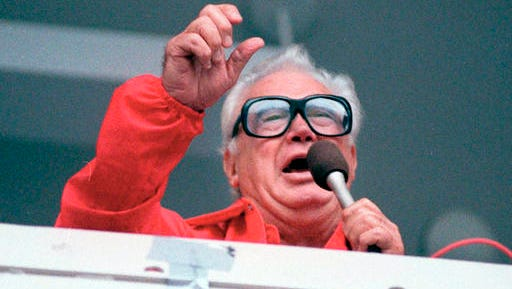 """FILE - In this July 21, 1989 file photo Chicago Cubs' broadcaster Harry Caray sings """"Take Me Out To The Ballgame"""" during the seventh inning stretch at Chicago's Wrigley Field.  Brewer Anheuser-Busch honored the legendary sportscaster, who died in 1998 having not seen his beloved Cubbies make it to the World Series, with a video that had him calling the end of Game 7, with the Cubs defeating the Cleveland Indians in an extra-inning 8-7 nail biter. The brewer also resuscitated 1984 Budweiser ad in which the Bud pitch man, and consumer, caught a cold one launched into the Wrigley Field bleachers using a net."""