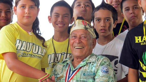 In this Nov. 22, 2013, file photo, Herb Weatherwax, then 96, poses for a photo with Hau'ula Elementary School sixth graders as he greets visitors to the Pearl Harbor Memorial in Hawaii.