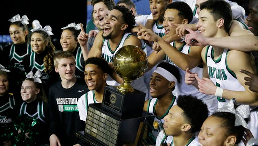 Kentwood players celebrate with the trophy after they won the the boys' CLass 4A high school basketball championship game against Union, Saturday, March 4, 2017, in Tacoma, Wash. (AP Photo/Ted S. Warren)