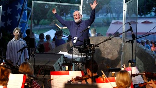 This handout photo provided by Capitol Concerts, shows John Williams conducting the National Symphony Orchestra and other musicians for the upcoming debut of a new arrangement of the national anthem, on Capitol Hill in Washington. It will be performed July 4 on the National Mall before the annual fireworks show.