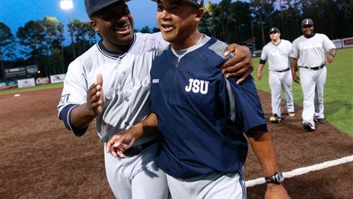 Jackson State third baseman Dylan Parker, left, celebrates with head coach Omar Johnson, right, after winning an NCAA college baseball tournament regional game against Louisiana-Lafayette in Lafayette, La., Friday, May 30, 2014. Jackson State won 1-0. (AP Photo/Jonathan Bachman)