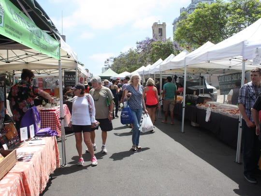 Shoppers stroll through Little Italy Mercato, a weekly