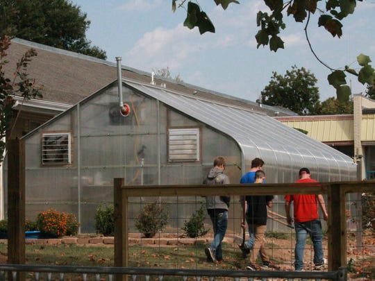 Students at Guy Berry College and Career Academy walk past the school's greenhouse Monday afternoon.