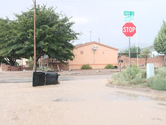 A trash can floats down 24th Street after a flood on