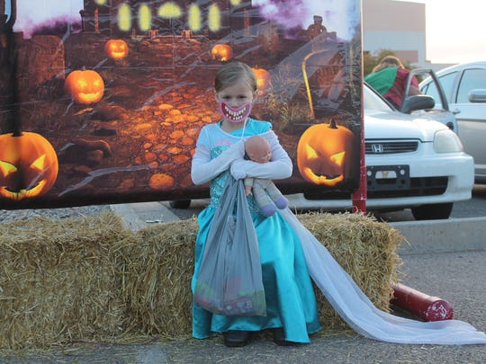June Ferguson, 4, sits in front of a Halloween backdrop at NMSU-A's Trunk-or-Treat event Tuesday evening.