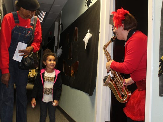 Kahlia Benson, 2 years old, enjoys Julianne Hall's saxophone music.
