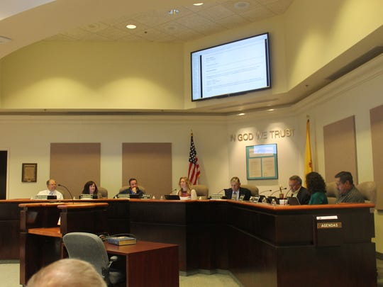 Commissioner Hudson takes his seat with fellow commissioners during Tuesday evening's meeting.