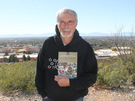 "New Mexico Museum of Space History Education Specialist Michael Shinabery stands with his book ""Legendary Locals of Alamogordo"" outside the New Mexico Museum of Space History Friday afternoon."