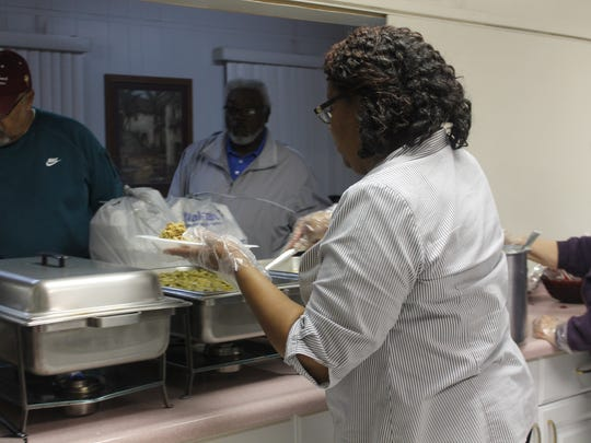A Corinth Baptist Church member serves a Thanksgiving meal to residents of the community. The church served up to 500 people.