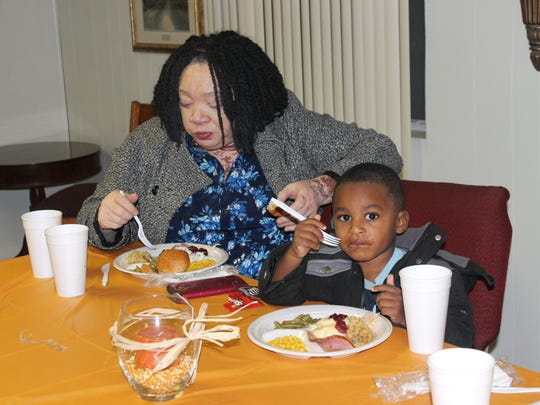 Carla Smith and her son Dewayne Smith feast on Thanksgiving meal provided by Corinth Baptist Church Tuesday evening.