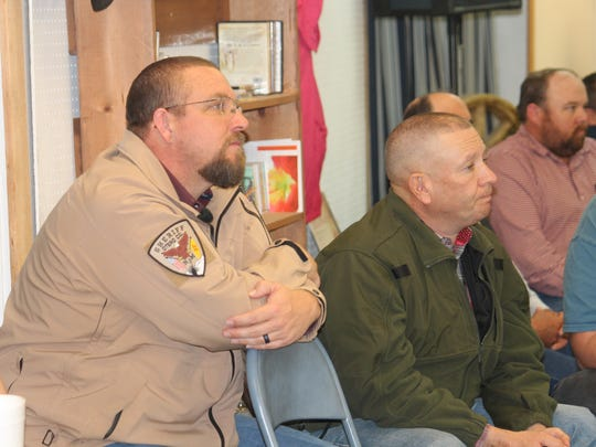 Otero County Sheriff Benny House and Otero County Undersheriff Darren Syling listen to County Commission Chairman Ronny Rardin speak at the Otero County Conservatives meeting Thursday evening at New Heart Cowboy Church.