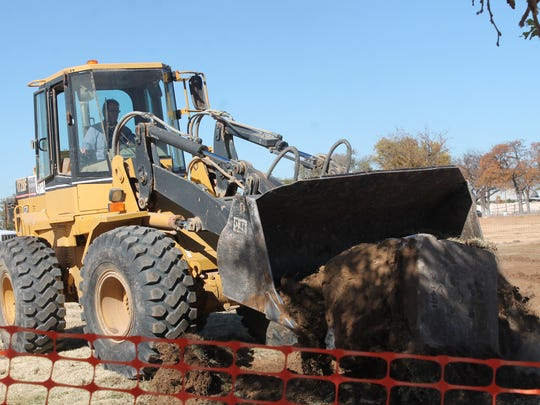 Workers use a wheel loader to pull concrete from the ground on Tuesday afternoon.