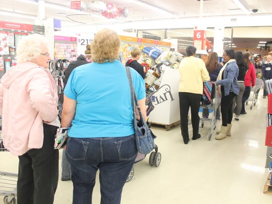 Shoppers wait in a long long line at Kmart Friday afternoon,