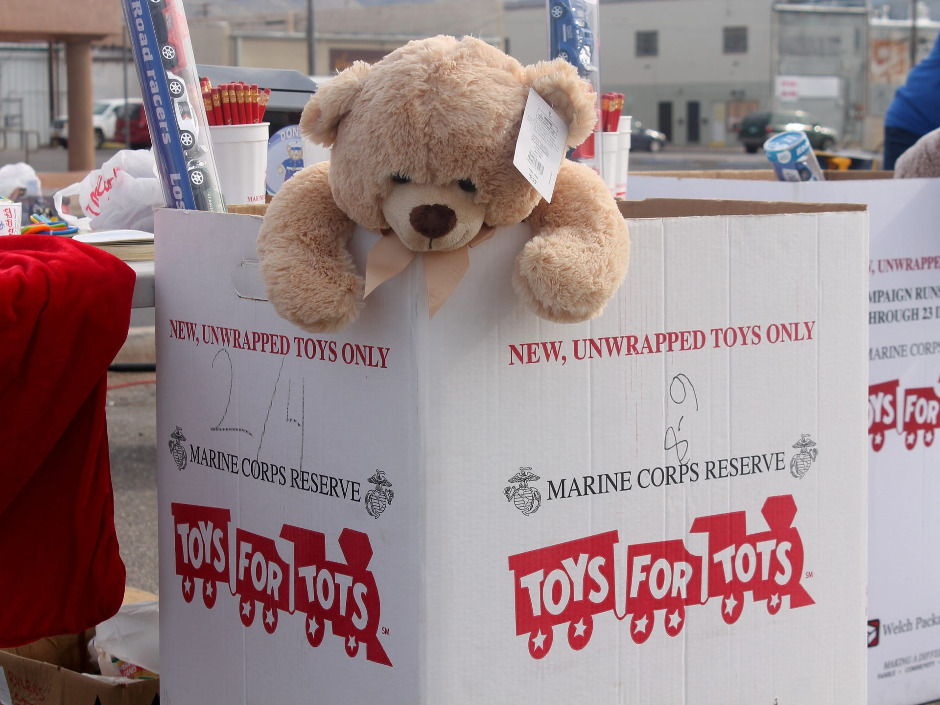 A Stuffed Teddy Bear In Toys For Tots Donation Box