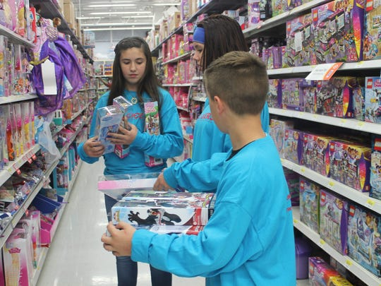 Big Givers shop for toys at Wal-Mart Tuesday evening for families in need.