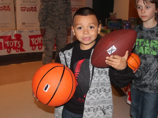 Desmond Macias stands with two gifts he picked out, a basketball and football, at the Otero County Toys for Tots Christmas event for children at the Sgt. Willie Estrada Memorial Civic Center on Christmas Eve.