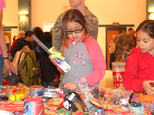 Marina and Angie Rodriguez pick out gifts at the Otero County Toys for Tots Christmas event for children at the Sgt. Willie Estrada Memorial Civic Center on Christmas Eve.