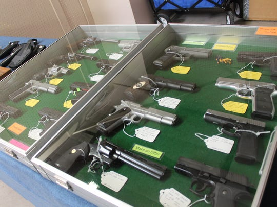 Handguns are displayed in glass cases during Saturday's