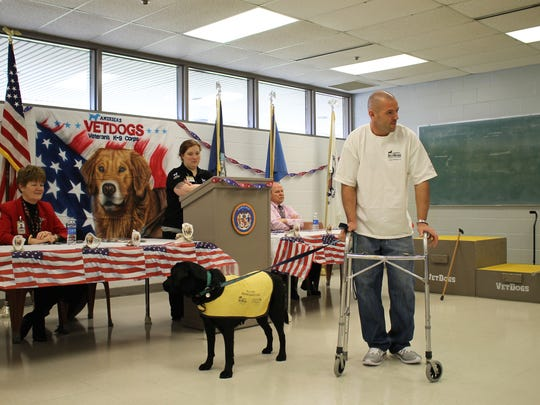Jeremy Lepone demonstrates how service dogs can assist disabled veterans with his trainee, Jennie during the America's VetDogs graduation ceremony Feb. 9, 2016 at the Eastern Correctional Institute in Westover, Maryland.