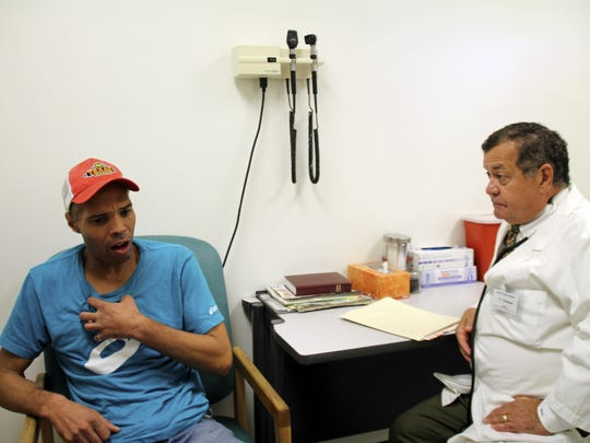 Bobby Allen visits the Asheville Buncombe Community Christian Medical Ministry. Allen, who does not have health insurance, seeks treatment for an ongoing cough from Dr. Keith Campbell, a retired family doctor who volunteers at the clinic.