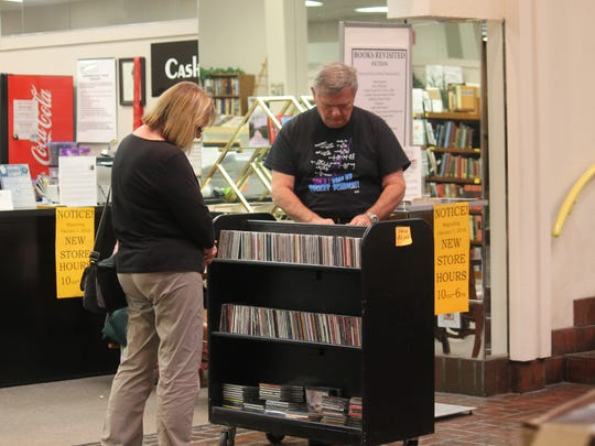 Customers browse a shelf of CDs during their visit to Books Revisited on Friday.