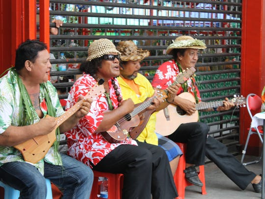 Singers perform on a Papeete street.