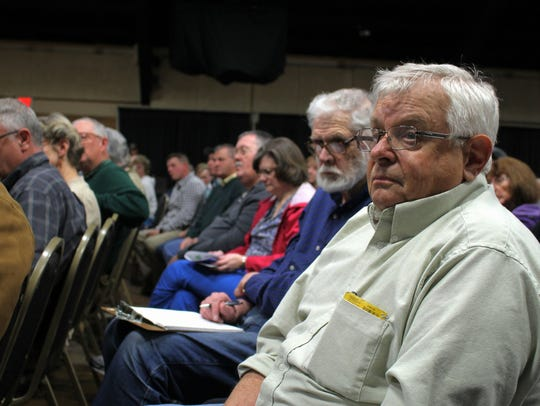 Audience members listen as speakers answers submitted