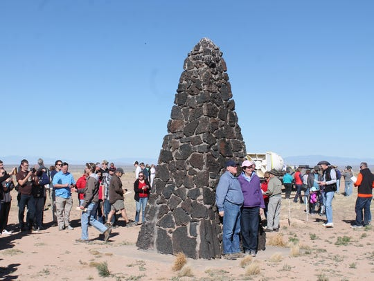 A couple stands in front of the Trinity Site obelisk