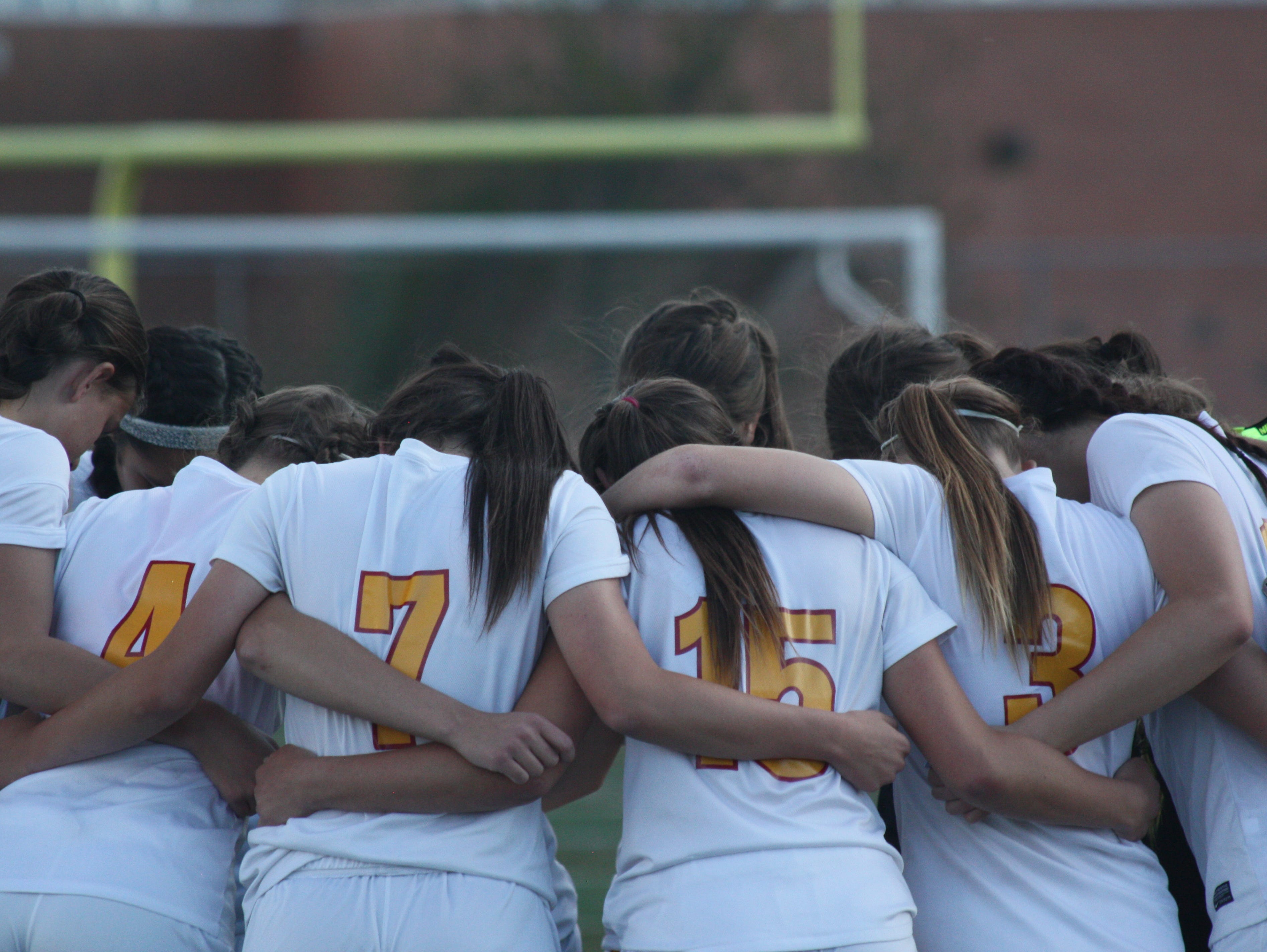 The Rocky Mountain girls soccer team huddles before playing Fort Collins on Saturday night. The Lobos won 5-0.