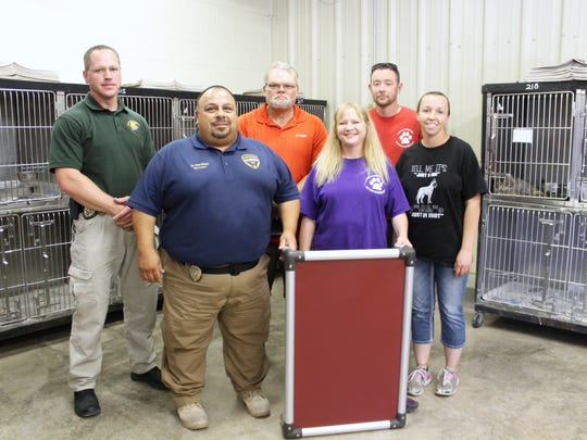 Michael Lawrence, Dwayne Martinez, Brian McIntosh, Tina McIntosh, Seth Rector and Sheri Thomas pose with one of the 19 beds they delivered to Animal Control on Friday.