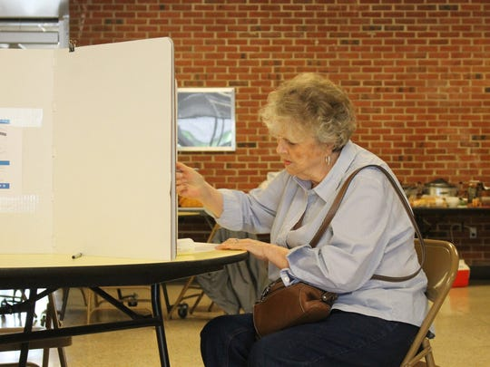 A voter fills out her ballot at WiHi on Tuesday.