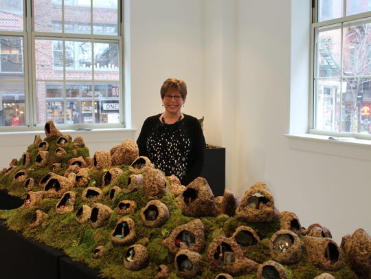 Artist Janet Williams stands with her caves of memories