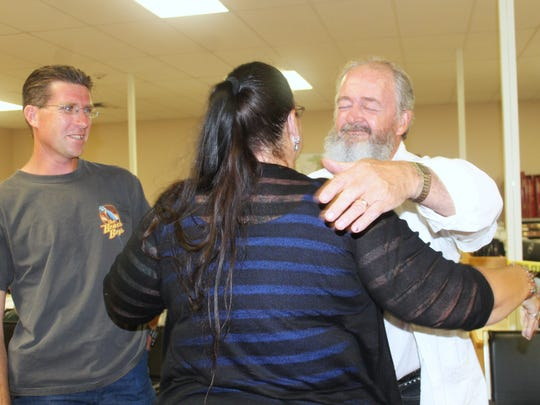 Bies hugs her opponents John Secrest and Josh Rardin after unofficially winning the County Commission seat.