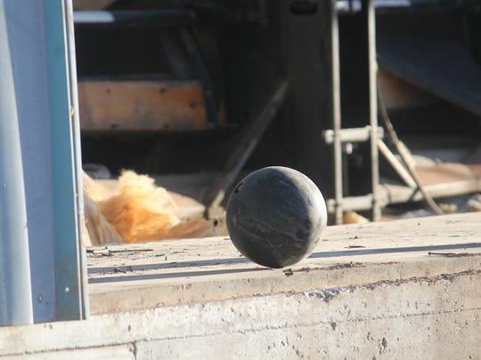 An abandoned bowling ball sits on the outskirts of the opened building.
