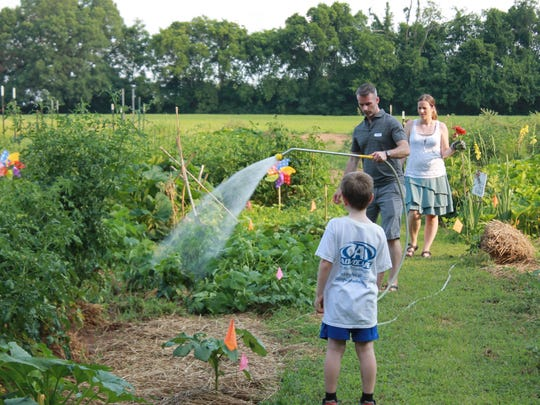 The Smith family of Christ Community Church tends to their plot in the Stewards Garden.