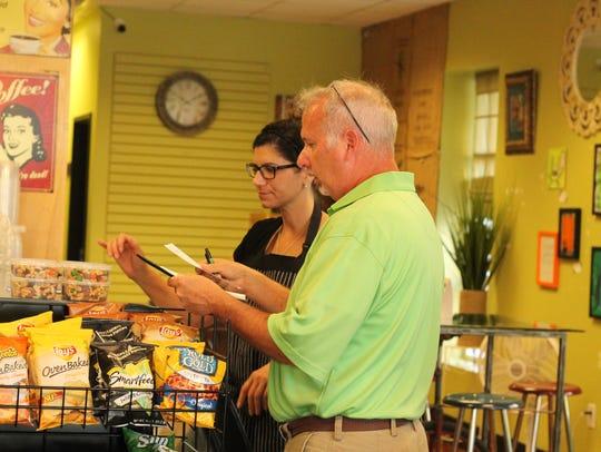 Darla Knight, left, talks to a customer inside Hops