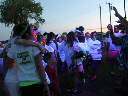 Participants in the inaugural UV Splash and Dash 5K gather to take photos under black lights.