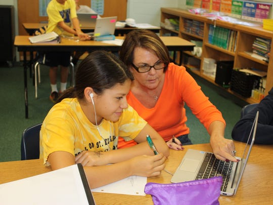 """Math teacher Teresa Miller, right, helps a student at her computer. Miller's """"flipped-blended"""" style of teaching allows her to give students individual attention while others are working with their computers."""