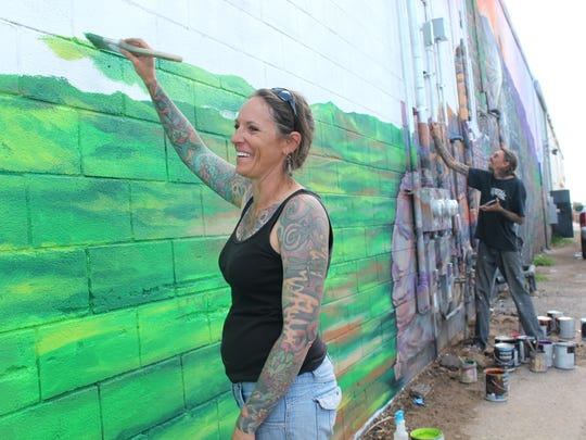 Angie and Justin Nowell, local artists, work on the downtown mural Friday morning.