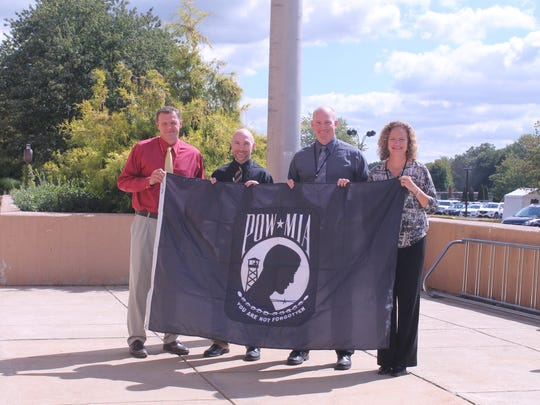 Left to right: Voorhees High School Athletic Director Brian Baumann, Assistant Principal Rich Broan, Principal Ron Peterson and Assistant Principal Susan Hammerstone display the new POW/MIA flag before it is hoisted.