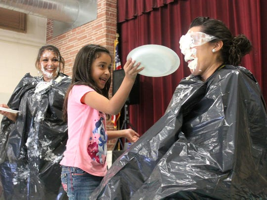 Chloe Purcell, second grader at Oregon Elementary, pies her teacher Melissa Felton during Thursday's assembly.