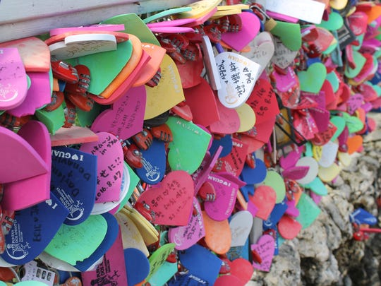 Hundreds of love notes left by tourists are attached to a rail at Puntan Dos Amantes Oct. 14, 2016.